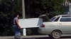Kazakhstan man uses his girlfriend to carry a FRIDGE while running behind his car