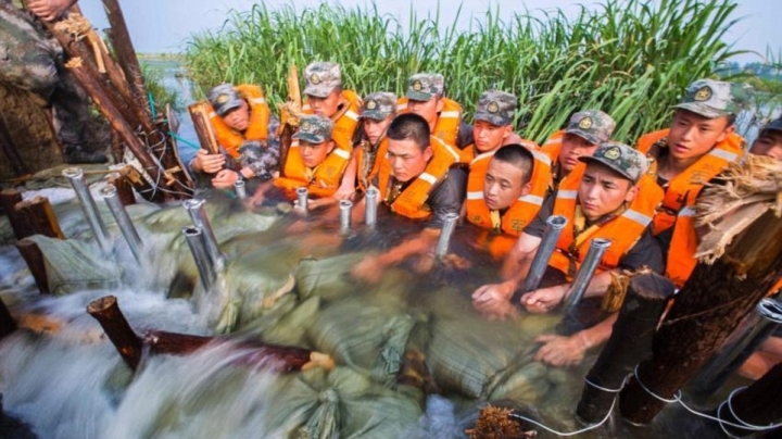 Chinese soldiers use their bodies to stop furious floodwaters from entering a city