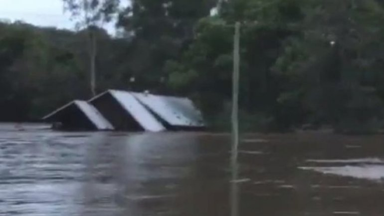 Australia floods: House washed away after family's rescue