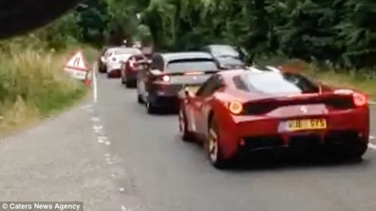 Is this the world's most expensive traffic jam? Stunned lorry driver spots 36 Ferraris worth a total of £7.2M queuing up at temporary lights