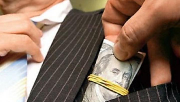 Inspector financiar, prins în flagrant cu mită. A cerut 200 de dolari pentru a aplica o amendă mai mică unui agent economic