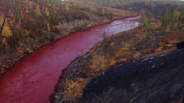 ÎNFIORĂTOR! Locuitorii sunt șocați după ce apa unui râu a căpătat culoarea sângelui (FOTO)