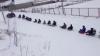 Distracţie periculoasă! Zeci de copii şi adulţi pe sănii sunt traşi de o maşină (VIDEO)