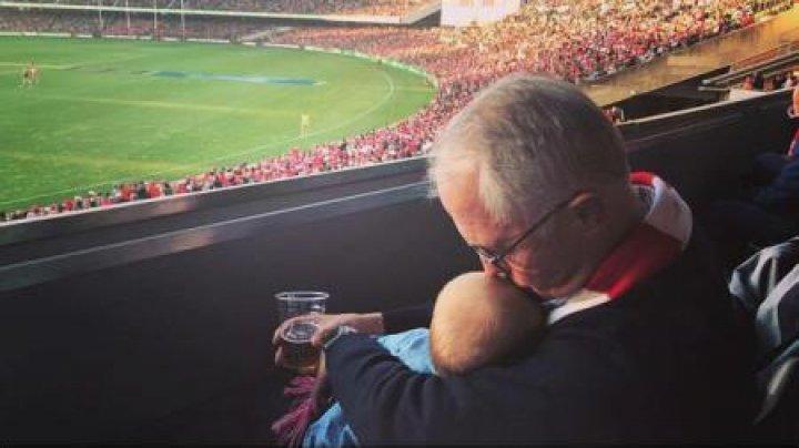 Reacţii diverse la fotografia premierului Australiei! Oficialul se afla la un meci de fotbal cu bebelușul într-o mână și cu o bere în cealaltă