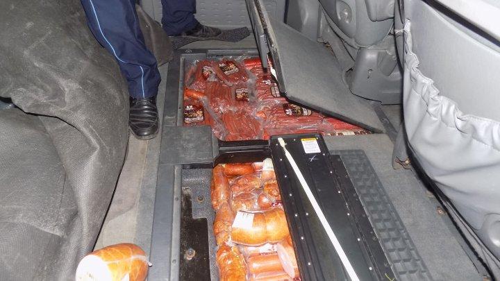 Un moldovean a încercat să aducă în ţară mezeluri din carne de porc ascunse în podeaua maşinii