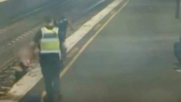 LA UN PAS DE MOARTE! O femeie a fost salvată în ultima clipă de pe șina de tren (VIDEO)