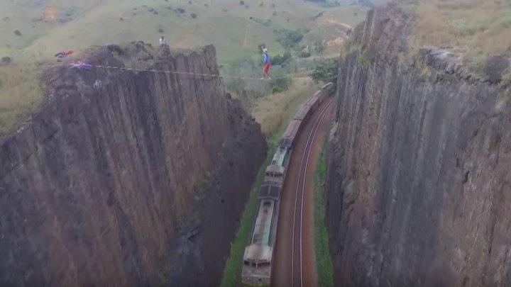 CASCADORIE ULUITOARE! Un bărbat a mers pe o sfoară întinsă între 2 stânci, în timp ce la sol se deplasa un tren (VIDEO)