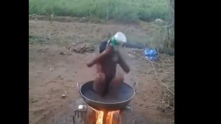Un băiețel se spală într-o oală pusă pe foc (IMAGINILE VĂ POT AFECTA EMOȚIONAL)