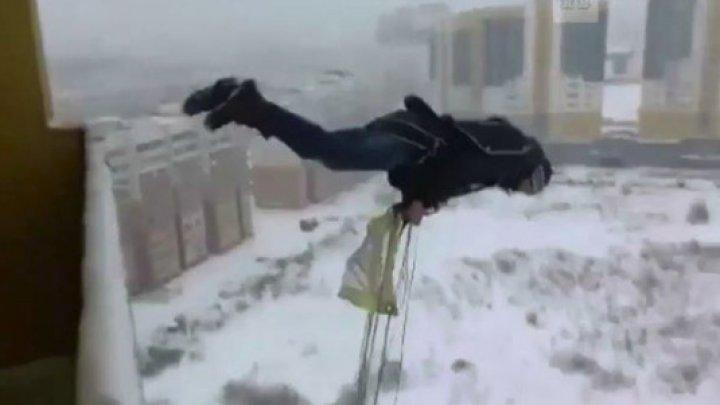 A decis să se JOACE CU MOARTEA! Cum a sărit un bărbat cu paraşuta de la balconul unui bloc (VIDEO)