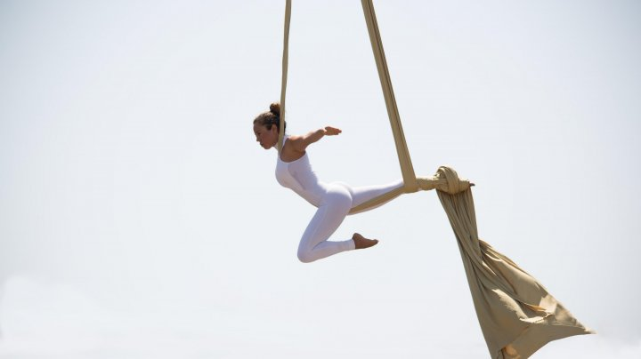 DANS ACROBATIC LA ÎNĂLŢIME. O tânără a făcut mişcări în aer fiind atârnată de pânze