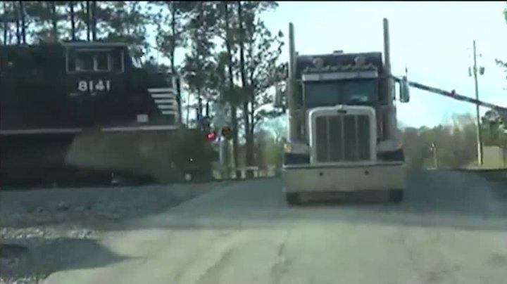 NO COMMENT! Un camion blocat pe o cale ferată a fost lovit în plin de un marfar (VIDEO)