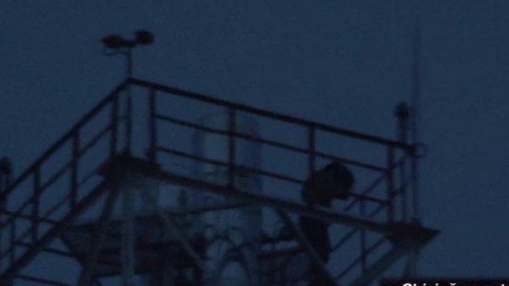 O femeie a stat cocoţată mai bine de cinci ore pe un turn situat în centrul Capitalei (VIDEO)