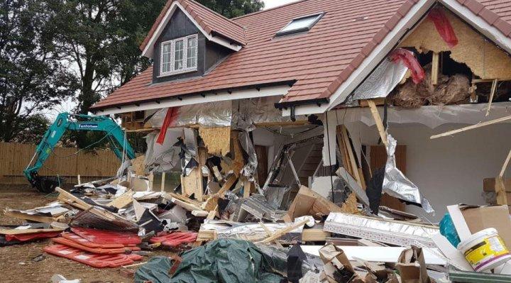 Un constructor român din Marea Britanie a distrus un cartier nou, cu un excavator