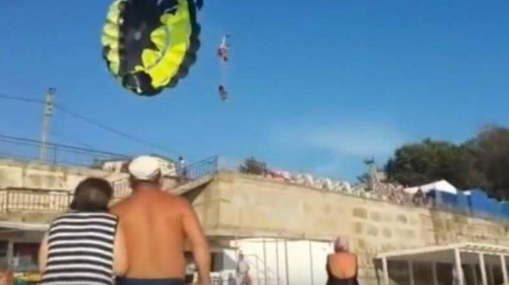 MOMENTUL DRAMATIC în care doi tineri cad cu parașuta de la 30 de metri, după ce se electrocutează de mai multe fire electrice