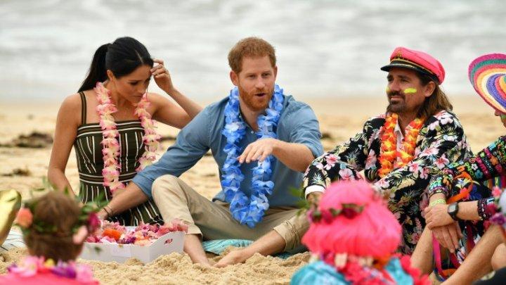 Prinţul Harry şi Meghan Markle, alături de surfişti australieni. Au fost surprinși în picioarele goale pe o plajă celebră