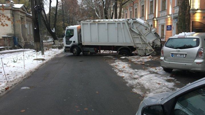GHINION: Un şofer s-a pomenit cu maşina blocată într-o groapă în centrul Capitalei (VIDEO)