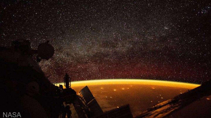 Imagine INCREDIBILĂ surprinsă de NASA. Ciudata strălucire portocalie a Pământului