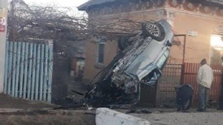 ACCIDENT SPECTACULOS. O şoferiţă de 19 ani s-a îmbătat şi s-a urcat cu maşina pe poarta unei case (FOTO)