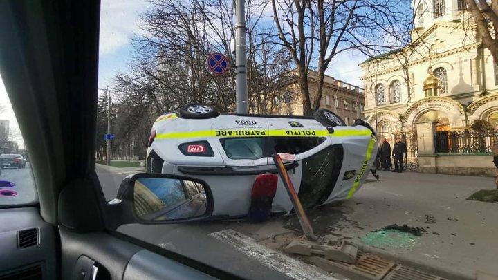 Accident cu implicarea unei mașini de poliție: S-a ciocnit cu un alt automobil și s-a răsturnat ( VIDEO)