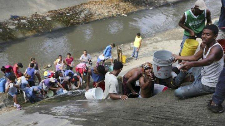 IMAGINI DRAMATICE ÎN VENEZUELA. Oamenii au început să bea apă din canal la aproape o săptămână fară electricitate (VIDEO)