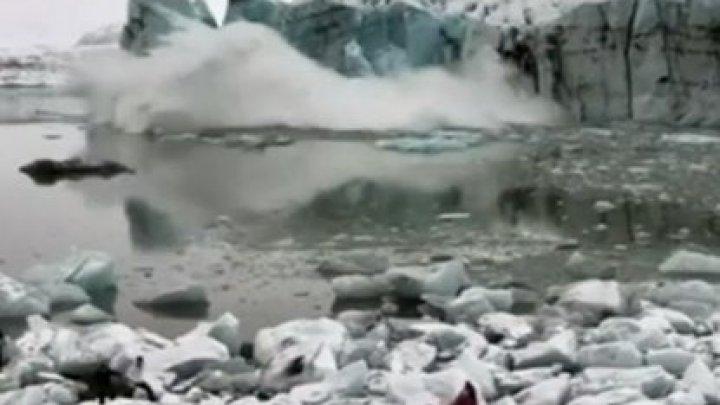 CLIPE DE SPAIMĂ pentru turiștii care vizitau un ghețar din Islanda. MOMENTUL în care sunt amenințați de un val uriaș de apă