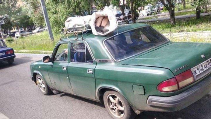 CAZ IEȘIT DIN COMUN! Un cadavru înfășurat într-un cearșaf, trasportat pe acoperișul unei mașini (FOTO)