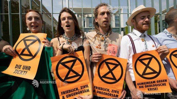 Activiştii ecologişti germani, legaţi cu lanţuri de grilajul cancelariei, pentru a denunţa o catastrofă climatică