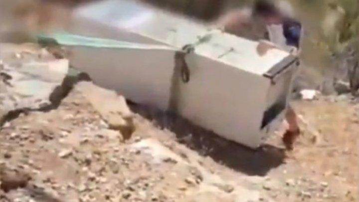Un bărbat, obligat de poliție să scoată un frigider din râpa în care l-a aruncat (VIDEO)