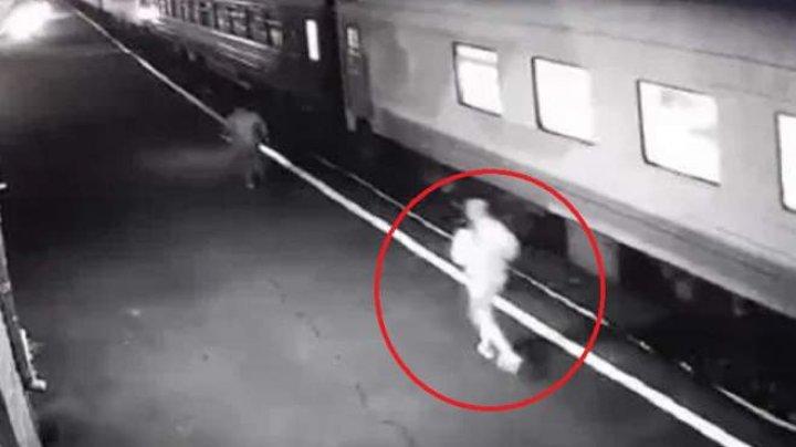 IMAGINI ŞOCANTE! Momentul în care o femeie alunecă sub șinele unui tren, sub privirile îngrozite ale călătorilor