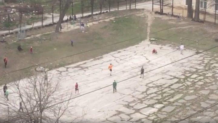 Iresponsabilitate totală: Mai multe persoane, surprinse în timp ce joacă fotbal pe un stadion din curtea unui bloc din Capitală (VIDEO)