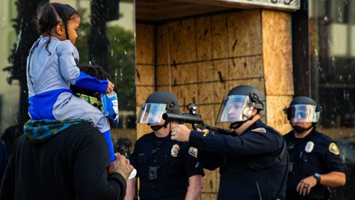 IMAGINE ŞOCANTĂ surprinsă în timpul protestelor din SUA. Polițist, cu arma scoasă și degetul pe trăgaci, în fața unei copile