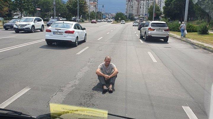 Gest iresponsabil! Un bărbat, surprins aşezat jos în faţa maşinilor chiar în mijlocul corosabilului (FOTO)