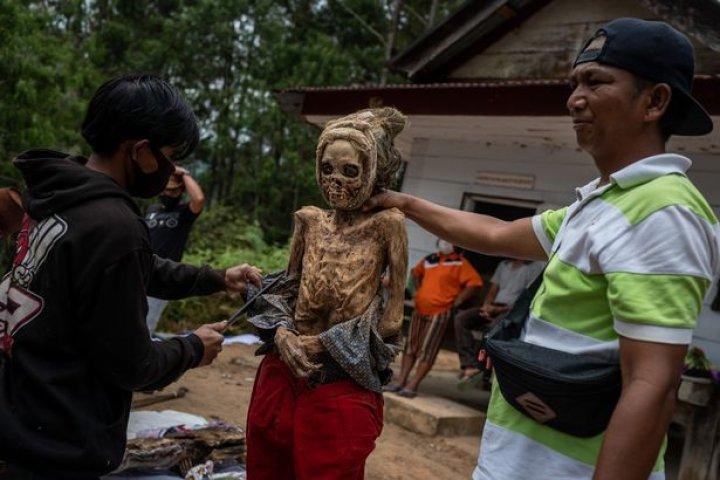 Ritual macabru pe o insulă din Indonezia: Oamenii își dezgroapă morții, le schimbă hainele și stau la o țigară cu ei (FOTO)