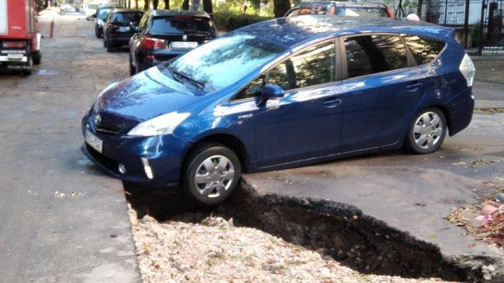 Ploaia a făcut ravagii în Capitală. Câteva mașini parcate au ajuns cu roțile în șanț, după ce apa a spălat pietrișul (FOTO)