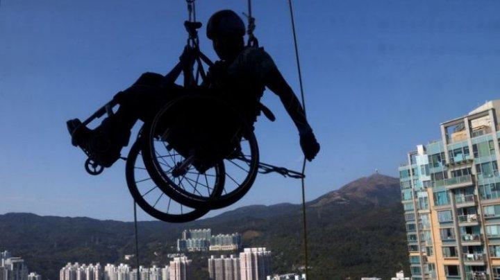 Un sportiv din Hong Kong a escaladat un zgârie-nori în scaun cu rotile