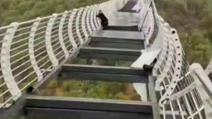 Un chinez a rămas agățat de un pod la 100 de metri înălțime, după ce panourile de sticlă s-au spart