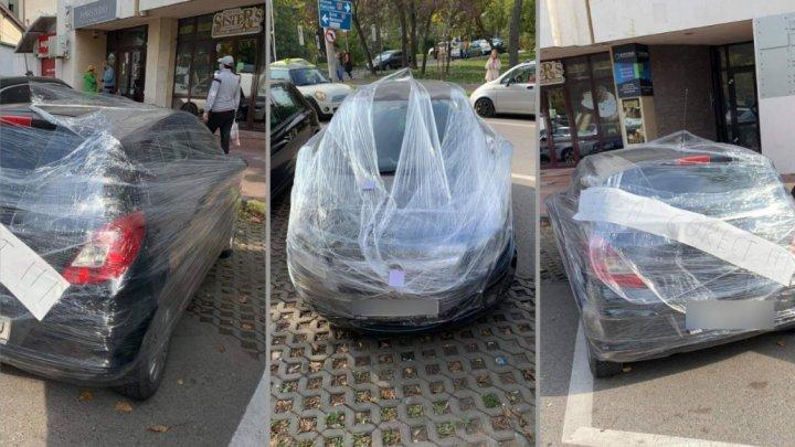 Lecţie de viaţă pentru un şofer. Bărbatul şi-a găsit maşina învelită în folie de plastic, după ce a parcat-o strâmb pe o stradă