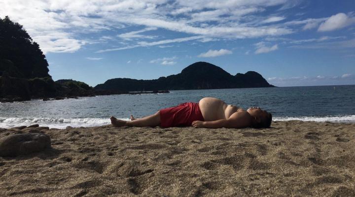 Пузатый турист лег на песок и повторил очертания горы