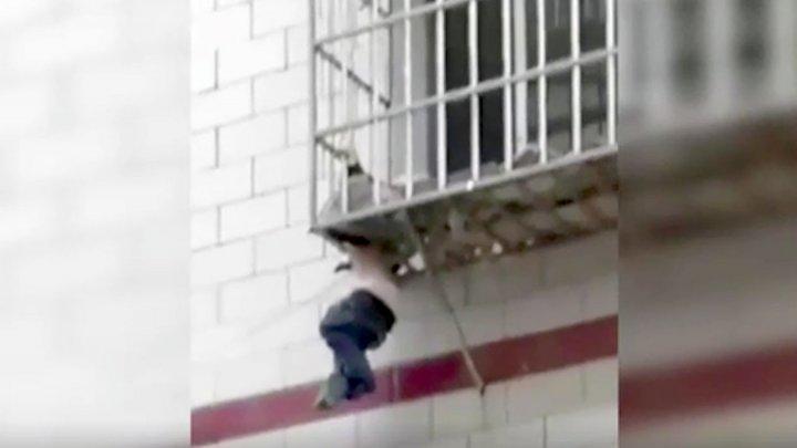 В Китае мальчик провалился в щель на балконе и повис на шее: видео