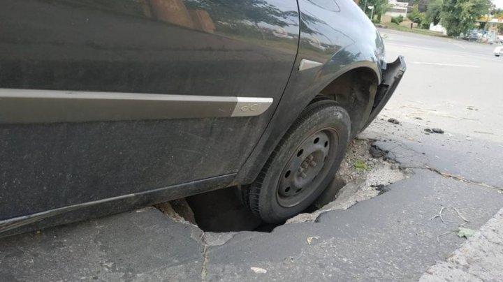 Машина провалилась в яму на дороге в центре столицы