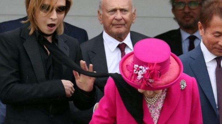 Королевская невозмутимость: Елизавету II прямо по лицу хлестнул чужой шарф (видео)